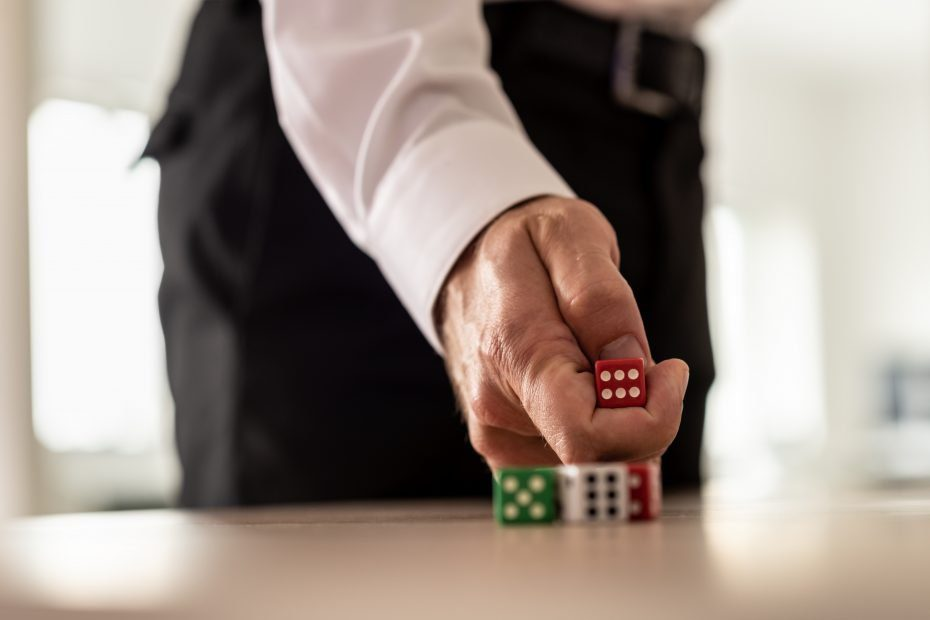 business man throwing red dice over an office desk.