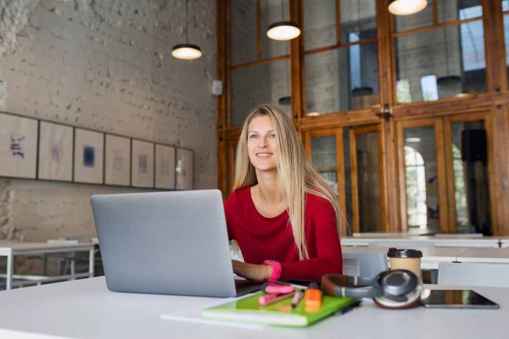 smiling women sat at laptop in co-working space