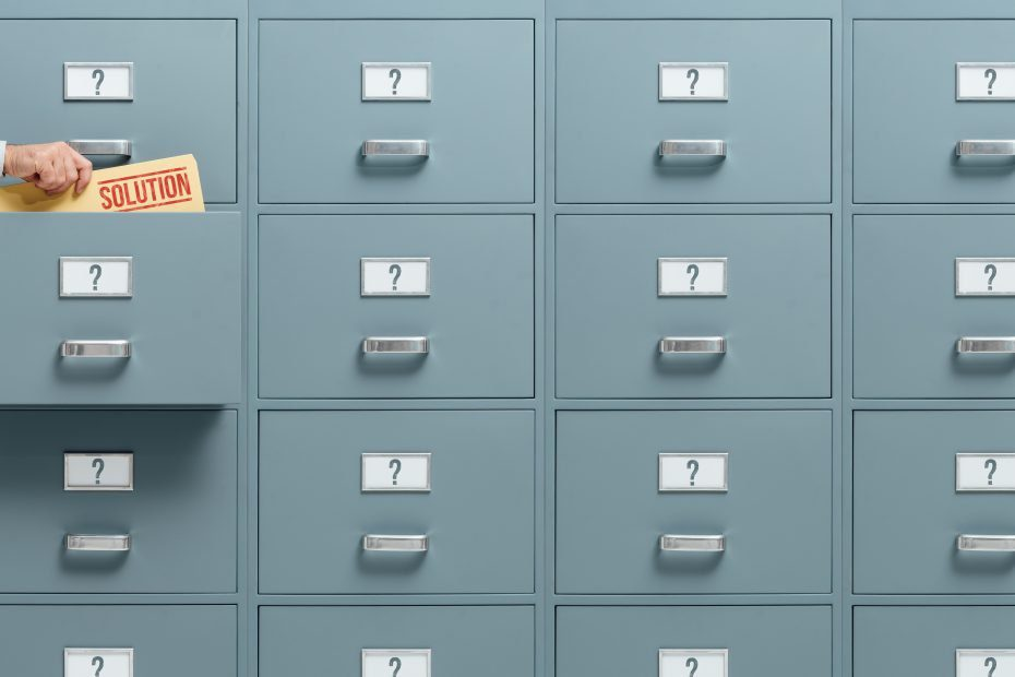 Businessman finding a file that holds a solution for his business plan in a filing cabinet drawer, problem solving and solution finding concept